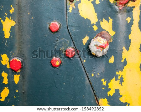 background of aged flaking paint on rusty iron with bolts