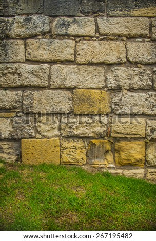 Background of ancient historical old retro vintage aged stone front yellow and gray wall texture in antique style Fresh spring green grass Empty space No people Backdrop of big large brick fence - stock photo