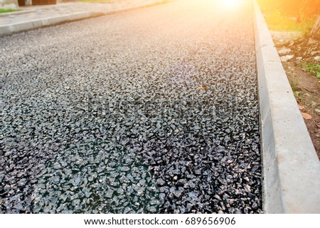 Background of black granules of fresh asphalt that been already paved.