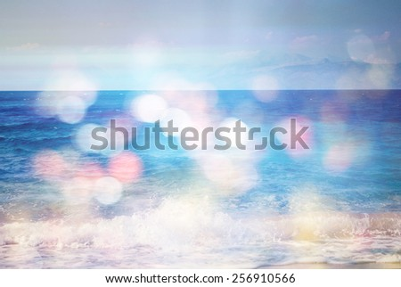 background of blurred beach and sea waves with bokeh lights, sandy beach  with turquoise water, bright white sun lights bokeh, travel and summer holidays concept - stock photo