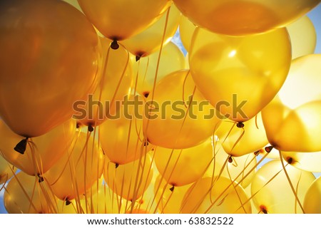 Background of  bright yellow inflatable balloons up in the air, backlit by sun. - stock photo