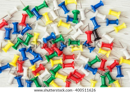 Background of coloured thumbtacks - office push pins. Office supplies. - stock photo