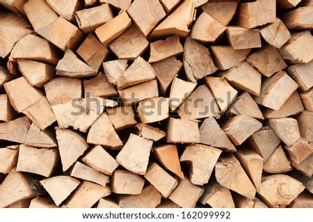 Background of dry chopped firewood logs in a pile. - stock photo