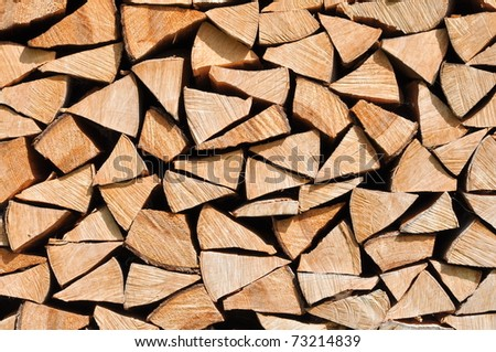 Background of dry Firewood Logs stacked up on top of each other - stock photo