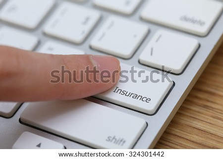 background of finger pushing on  insurance button on laptop  keyboard