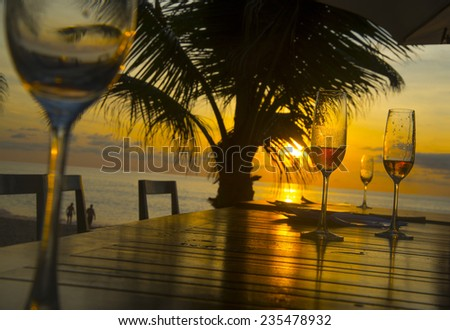 Background of four glasses champagne vine staying on wooden table chairs against palm silhouette sunset yellow sky with clouds couple in water on coast and sun light reflection on boards After dinner  - stock photo