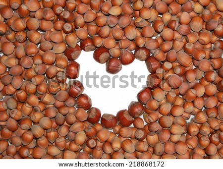 background of fresh hazelnuts in the nutshell and heart shaped copy space - stock photo