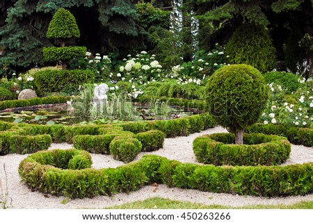 Background of garden design. Landscaping in park with pond, shorn trees and lawn - stock photo