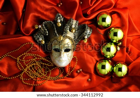 Background of golden Christmas tree balls with gold decorations and golden mask on red shiny silk fabric with dramatic light and shadow