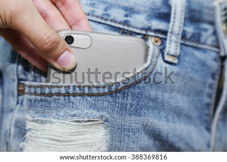 background of hand stealing a mobilephone from woman jeans pocket - stock photo