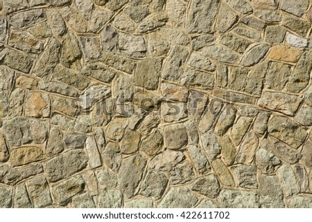 Background of irregular stone blocks. Rough texture on weather worn stone.