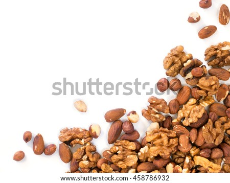 Background of mixed nuts - hazelnuts, walnuts, almonds - with copy space. Isolated one edge. Top view or flat lay - stock photo