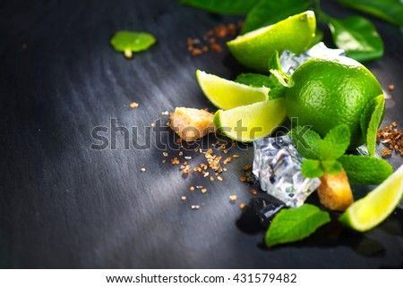 Background of Mojito cocktail ingredients on a table in summer bar, Alcohol cocktails with Rum, lime, mint, ice cubes and brown sugar closeup, Party drink. Isolated on black background, - stock photo