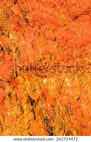 Background of natural wet orange stone wall texture rough rock surface - stock photo