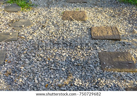 Background of pebble and wooden piece  make for the walk path in the park. with sun light in the morning.