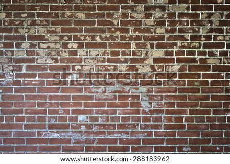 Background of red brick wall with textured peeling paint with dark vignette - stock photo