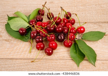 Background of ripe cherries. Pile of fresh and tasty cherries. Fresh cherries scattered on a wooden table.  - stock photo