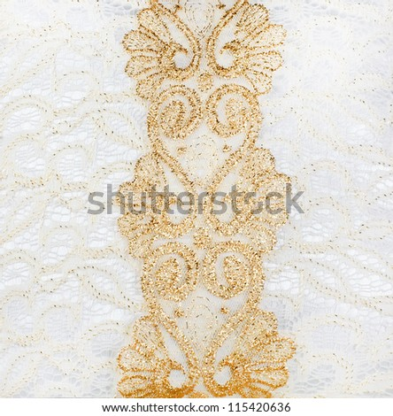 background of the Golden lace with rich ornaments and white satin covered with white lace with a big bow and waves tissue occupying the entire surface of the background - stock photo