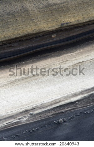 Background of volcanic and strata layers of ancient rock formation. - stock photo