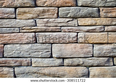Background of wall with rough solid stone arranged in layers - stock photo