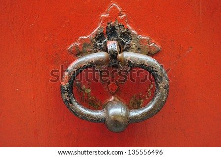 background old iron red door knocker - stock photo
