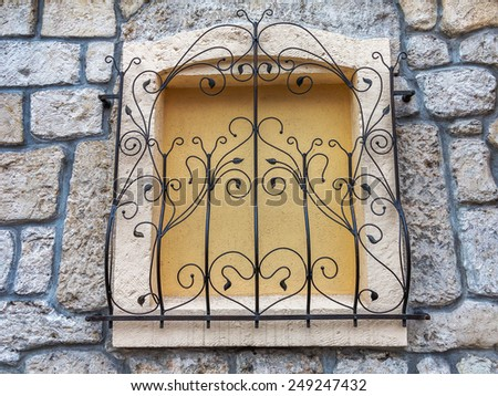 Background old stone wall with metal grille - stock photo