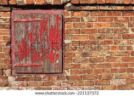 background patterns and texture of an old red brick wall and weathered wooden door with traditional hand made hinges