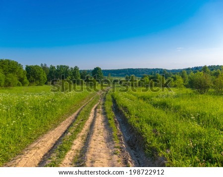 background picturesque landscape green field blue sky and wide country road leading to the forest - stock photo