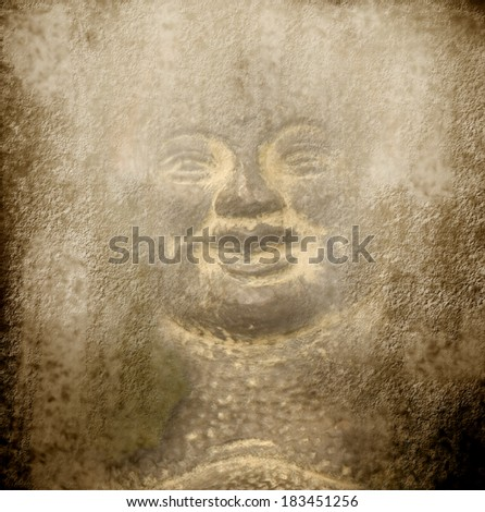 background smiling Buddha carved into a stone wall - stock photo