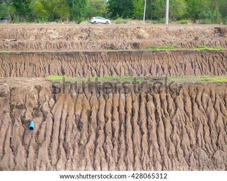 Background Soil coastal canal, which was rain water flow erosion and cars cruising on rural roads. - stock photo