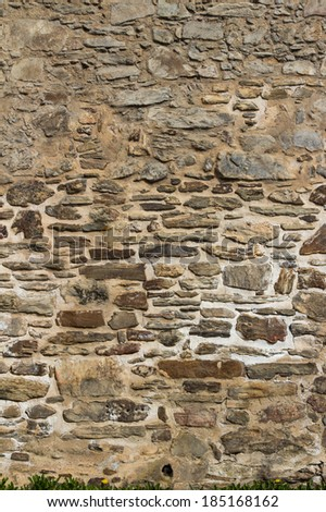 Background texture and pattern of a natural rough stone wall with uncut sandstone rocks in mortar in an architectural concept, full frame - stock photo