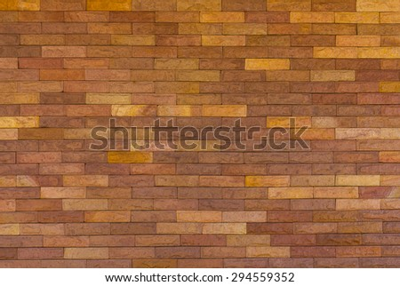 Background texture brown brick walls alternating with yellow variety is seamless. - stock photo