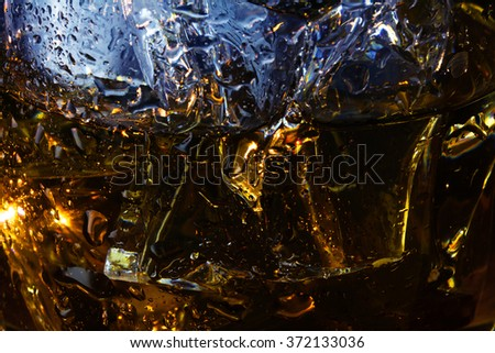background texture, detail of a whiskey glass with ice cubes, close up shot with with selected focus and narrow depth of field - stock photo