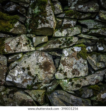 Background Texture Detail Of An Old Dry Stone Wall In Scotland - stock photo