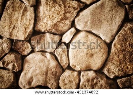 background texture of a wall built of natural stone close-up, toned photo