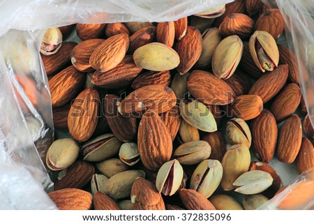 Background texture of assorted mixed nuts including almonds and pistachio nuts in open pack - stock photo