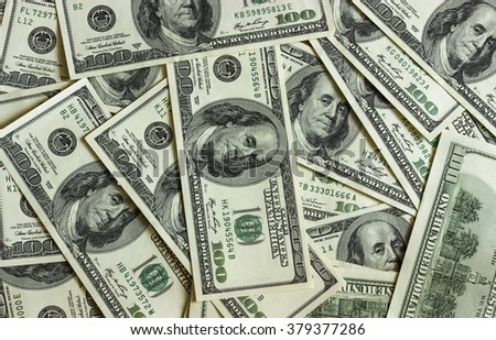 Background texture of banknotes in denominations of one hundred dollars scattered on a table - stock photo