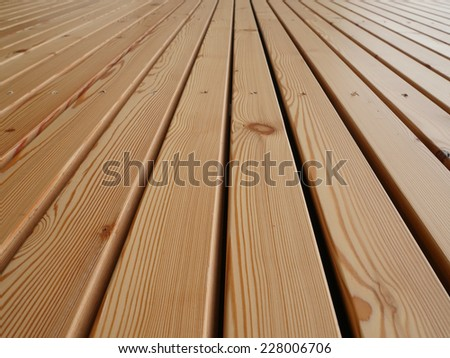 Background texture of finely slatted natural brown wood in a parallel pattern used in building decor and construction - stock photo