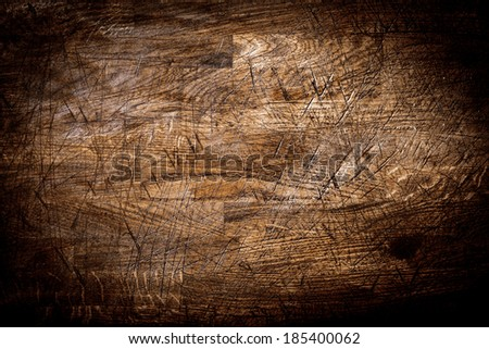 Background texture of old grungy scored wood with crisis-crossed cut marks from a knife and a heavy vignette - stock photo
