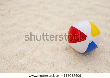 background with a beach ball in the sand - stock photo