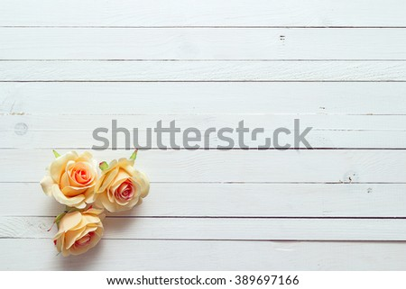 Background with a three peach roses on painted wooden planks. Place for text.