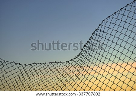 Background with chain link fence on evening sky - stock photo