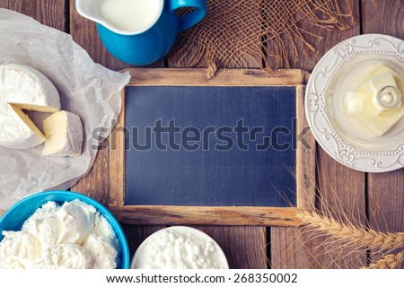 Background with chalkboard and dairy products. Focus on chalkboard. View from above - stock photo