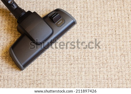 background with copy space. closeup cleaning with black vacuum cleaner hoover dirty, dusty floor beige carpet. housework. - stock photo
