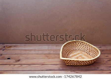Background with empty basket heart shape on wooden table - stock photo
