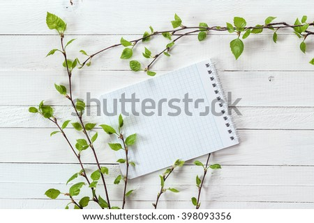 Background with empty notebook for text and fresh spring sprigs with young leaves on white painted wooden planks. Place for text. Top view with copy space