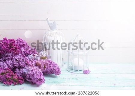Background  with fresh lilac flowers and candles in decorative bird cages in ray of light   on turquoise painted wooden planks against white wall. Selective focus. Place for text. - stock photo