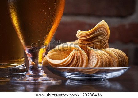 background with glass of Fresh Beer and plate full of chips - stock photo