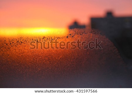 Background with ice, morning sunlight and silhouettes of houses on winter window glass - stock photo