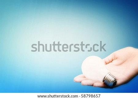 Background with lit lightbulb. Isolated on blue - stock photo